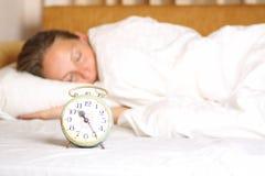 Jonge slaapvrouw en wekker in bed Royalty-vrije Stock Afbeeldingen