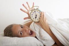 Jonge slaapvrouw en wekker in bed Royalty-vrije Stock Foto's