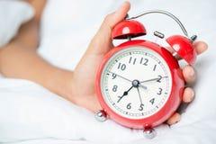 Jonge slaapvrouw en wekker in slaapkamer royalty-vrije stock afbeelding