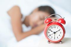 Jonge slaapvrouw en wekker in slaapkamer royalty-vrije stock afbeeldingen