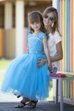 Jonge slanke blonde glimlachende moeder, tante of zusteromhelzingen kleine prett stock afbeeldingen