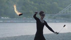 Jonge slanke mens in zwarte kleren en masker die een show met vlam uitvoeren die zich op riverbank bevinden Bekwame fireshowkunst stock video