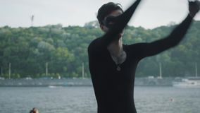 Jonge slanke mens in zwarte kleren en masker die een show met vlam uitvoeren die zich op riverbank bevinden Bekwame fireshowkunst stock videobeelden