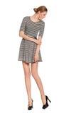 Jonge slanke modieuze vrouw die in die kleding met lange benen neer op de schoenen kijken, op witte achtergrond wordt geïsoleerd  stock foto's
