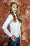 Jonge slanke mooie jonge blonde vrouw met lange benen en haar in Tumultoverhemd en jeans Royalty-vrije Stock Fotografie
