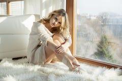 Jonge slanke sexy vrouw in bruine sweater tegen het venster stock fotografie
