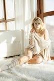Jonge slanke sexy vrouw in bruine sweater tegen het venster royalty-vrije stock fotografie