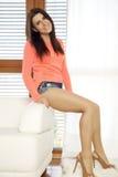 Jonge slanke vrouw in oranje sweater tegen het venster Stock Foto's