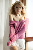 Jonge slanke sexy vrouw in roze sweater tegen het venster Stock Fotografie