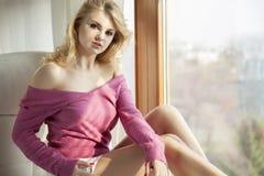 Jonge slanke sexy vrouw in roze sweater tegen het venster Royalty-vrije Stock Foto's
