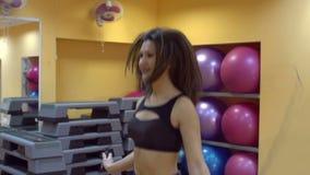 Jonge slanke vrouw die met touwtjespringen in gymnastiek, langzame motie springen stock footage
