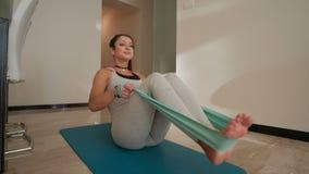 Jonge slanke vrouw die oefeningen met elastische geschiktheid op blauwe mat doen stock videobeelden