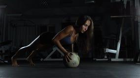Jonge slanke vrouw die wat gymnastiek doen bij de gymnastiek met bal stock video