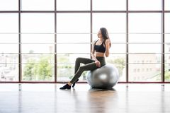 Jonge slanke Vrouw in sportkleding die haar abs op een Pilates-bal van fitball uitoefenen dicht omhoog bij gymnastiek Het concept stock afbeelding