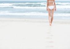 Slank meisje die in wit zwempak aan oceaan lopen. Royalty-vrije Stock Foto's