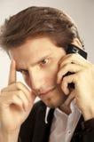 Jonge slimme mens die met telefoon wordt geconcentreerd Stock Foto