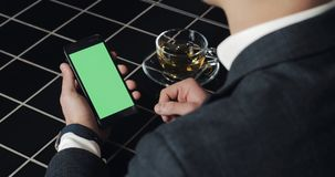 Jonge smarthpone van het zakenmangebruik met greenscreen touchpad en dicht omhoog gesturing in koffie Kerel die cellulair, het on stock videobeelden