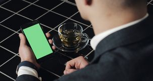 Jonge smarthpone van het zakenmangebruik met greenscreen touchpad en dicht omhoog gesturing in koffie Kerel die cellulair, het on stock footage