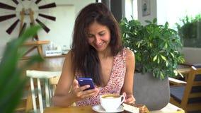 Jonge smartphone en de glimlach van het vrouwengebruik Het babbelen met vriend stock video
