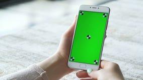 Jonge smartphone van het vrouwengebruik met het groene scherm stock video