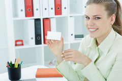 Jonge smilling secretaresse die leeg leeg document kaartteken met exemplaarruimte tonen voor tekst Stock Fotografie