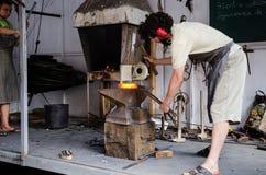 Jonge smiths die metaal onderwijzen te smelten en te vormen stock afbeelding