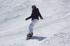 Jonge snowboardervrouw die bergaf glijden Royalty-vrije Stock Fotografie