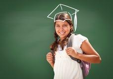 Jonge Spaanse die Student Girl Wearing Backpack Front Of Blackboard met Brandweermanhelm in Krijtoverheadkosten wordt getrokken royalty-vrije stock afbeelding