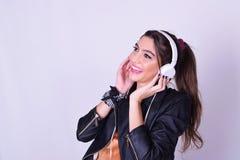 Jonge Spaanse vrouw die aan muziek met hoofdtelefoons luisteren Royalty-vrije Stock Foto