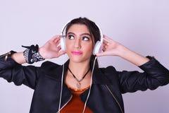 Jonge Spaanse vrouw die aan muziek met hoofdtelefoons luisteren Stock Fotografie