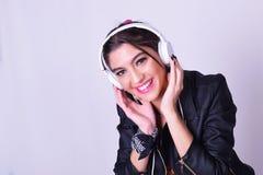 Jonge Spaanse vrouw die aan muziek met hoofdtelefoons luisteren Stock Afbeeldingen