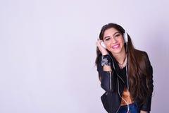 Jonge Spaanse vrouw die aan muziek met hoofdtelefoons luisteren Royalty-vrije Stock Foto's