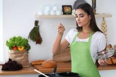 Jonge Spaanse vrouw in het groene schort koken in de keuken terwijl het blazen bij houten lepel De huisvrouw vond een nieuw recep royalty-vrije stock foto
