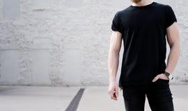 Jonge spier gebaarde mens zwarte t-shirt dragen en jeans die buiten stellen Witte bakstenen muur op de achtergrond stock foto
