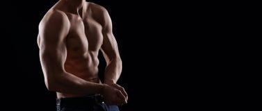 Jonge spiermens die zijn spieren tonen en op zwarte backg stellen royalty-vrije stock afbeeldingen