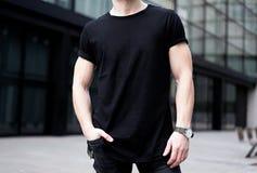 Jonge spiermens zwarte t-shirt dragen en jeans die in centrum van moderne stad stellen Vage achtergrond Hotizontalmodel royalty-vrije stock foto
