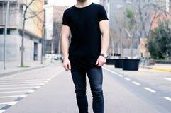 Jonge spiermens zwarte t-shirt dragen en jeans die op de straat van de moderne stad stellen Vage achtergrond stock foto's