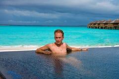 Jonge sportenmens in de pool en oceaan in de rug Royalty-vrije Stock Foto's