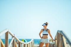 Jonge sportenvrouw bij zeekust het ontspannen na training stock afbeeldingen