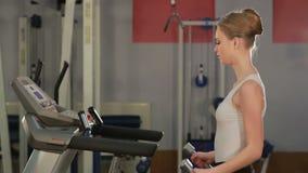 Jonge sportenvrouw die oefeningen met domoren in de gymnastiek doen Geschiktheid stock videobeelden