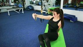 Jonge sportenvrouw die telefoon, meisjesatleet selfie in de gymnastiek, Mededeling in Internet met behulp van, fitness, levenssti stock videobeelden