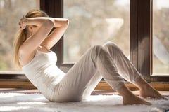 Jonge sportieve aantrekkelijke vrouw die de oefening van de rotspers thuis doen royalty-vrije stock foto's