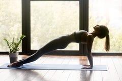 Jonge sportieve geschikte vrouw die Purvottanasana-oefening doen royalty-vrije stock foto