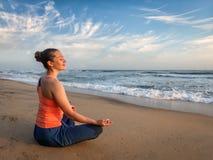 Jonge sportieve geschikte vrouw die yogaoudoors doen bij strand Stock Foto
