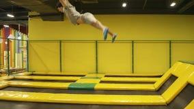 Jonge sportieve jongen die de tijd van zijn het leven genieten hebben die op trampoline springen Het uitvoeren van handspring tik stock videobeelden