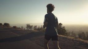 Jonge sportieve jonge mens die op bergweg lopen stock video