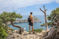 Jonge sportieve mens met rugzak die zich op de bovenkant van rots bevinden royalty-vrije stock fotografie