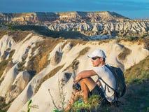 Jonge sportieve mens in wit GLB met rugzakzitting op de piek van zandsteen rots en het letten op aardlandschappen royalty-vrije stock foto's