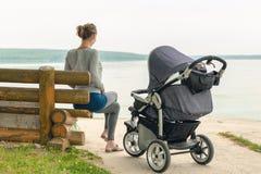 Jonge sportieve moeder met wandelwagenzitting op houten bank dichtbij meer of rivier Mamma die met baby in kinderwagen dichtbij v royalty-vrije stock foto