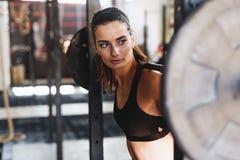 Jonge sportieve vrouw die barbell voorbereidingen treffen stock foto's